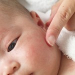 Close-up of an adult touching baby's face